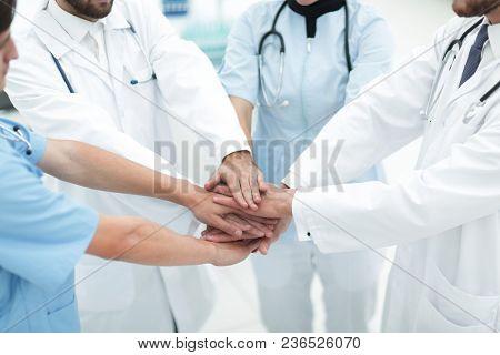 doctors holding hands together at hospital