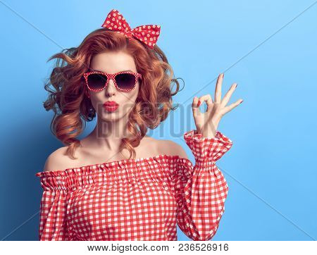 Pinup Portrait Beauty Redhead Girl Blowing Lips. Fashion Playful Woman Showing Ok Sign. Presenting Y