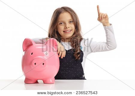 Little girl with a piggybank sitting at a table and holding her index finger up isolated on white background