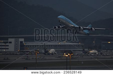 Korean Air Aircraft Taking Off From Hong Kong Airport Right After Sunset With The Airport Lights Beg