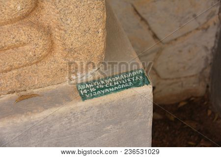 A Sign With A Sculpture In The Hampi Museum. Buddha Stone Lies In The Open-air Museum In Hampi, Indi