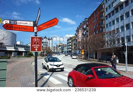 Helsingborg, Sweden - 14 April, 2018: Bicycle path sign with names of main tourist attractions and traffic on Drottninggatan street. Helsingborg is a port city located in southern Sweden