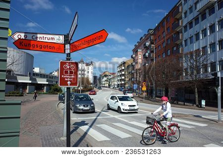 Helsingborg, Sweden - 14 April, 2018: Girl in pink helmet cycling pedestrian crossing on Drottninggatan street. Helsingborg is a port city located in southern Sweden
