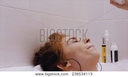 Young Attractive Woman Relaxing In Bath With Foam At Home. Woman With Headphones Taking A Bath.