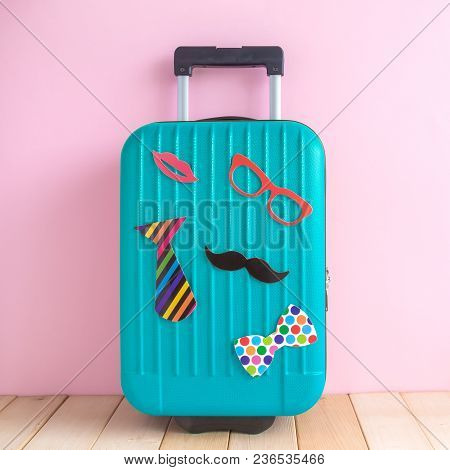 Suitcase With Paper Props Against Pastel Pink Wall Minimal Creative Tourism Concept.