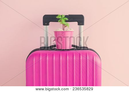 Suitcase With Small Bucket Full Of Sand And Palm Tree Against Pastel Pink Background Minimal Summer