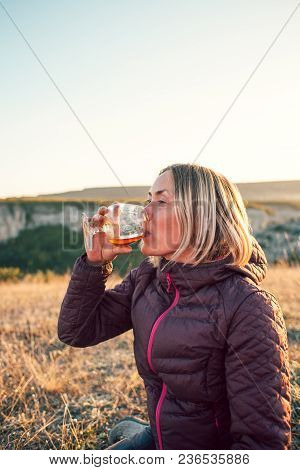 A Woman Drinks From A Glass. The Girl Is Sitting On The Background Of The Field. The Blonde Drinks A