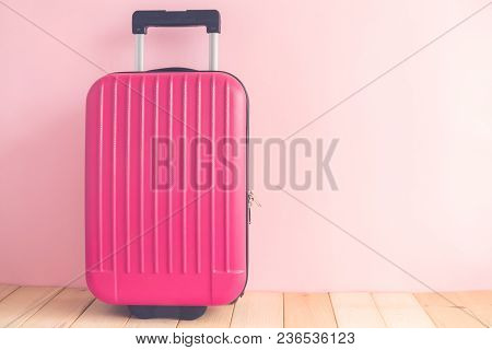 Pink Suitcase Against Pastel Rose Wall Minimal Travel Vacation Creative Concept. Space For Copy.