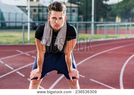 Young athlete stretching on racing track before running