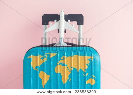 Suitcase With World Map And Airplane Model Toy Against Pastel Pink Background Minimal Travel Vacatio