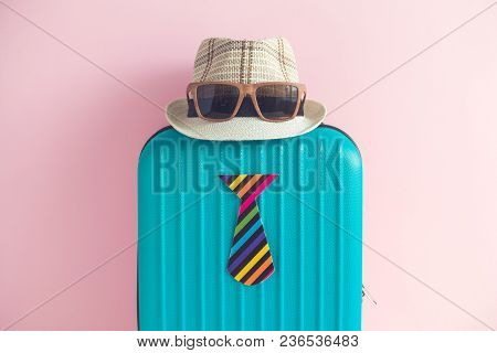 Blue Suitcase With Hat, Sunglasses And Paper Tie On Pastel Pink Background Minimal Travel Creative C
