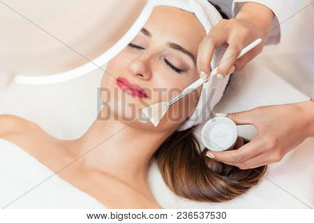 Close-up of the face of a beautiful woman relaxing during facial treatment with moisturizing cream for sensitive skin in a modern beauty center