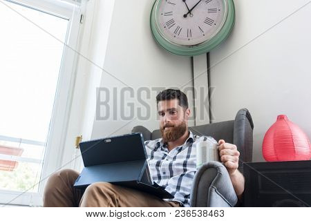 Young creative man sitting on armchair and holding a coffee mug while working on a tablet connected to internet in a modern co-working space