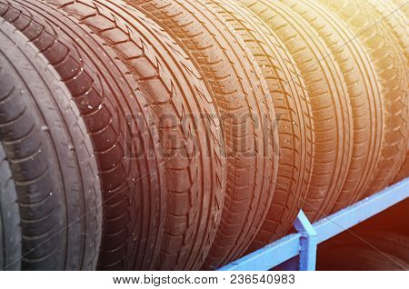 Rack With Variety Of Car Tires In Automobile Store. Many Black Tires. Tire Stack Background. Selecti