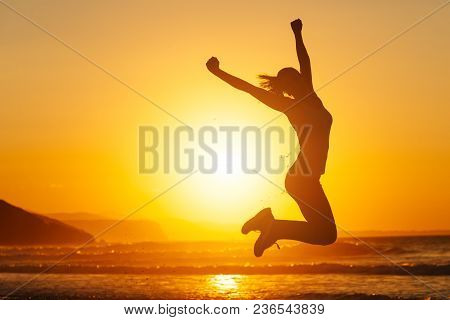 Silhouette Of Happy Joyful Woman Jumping And Having Fun At The Beach Against The Sunset. Freedom And