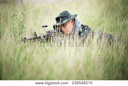 Sniper Laying On The Grass Looking Through Scope At The Target.