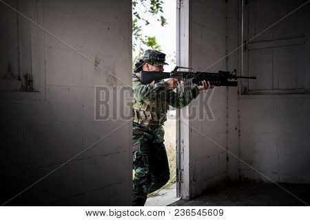 Special Forces Soldier Or Private Military Holding Gun Aiming Behind Concrete Obstacle In Urban Area