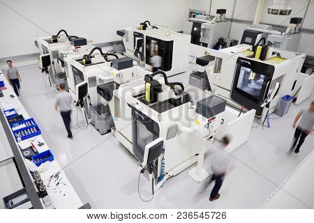 Overhead View Of Engineering Workshop With Workers Using CNC Machinery