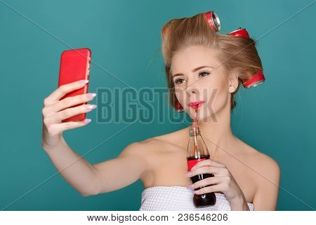 Beautiful Fun Curly Blond Woman Holding Glass Bottle With Soda And Making Selfie On Phone