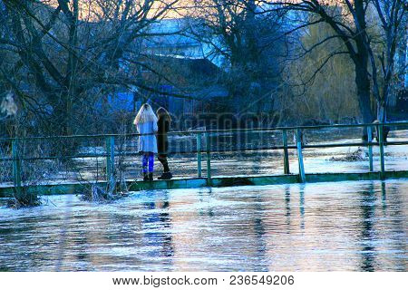 Young Girls Are Photographed On Background Of Flooding In Spring. Flooding Of River In Spring In Tow