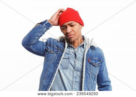 Ethnic Man In Denim Scratching Head Looking Indecisive And Puzzled On White Backdrop.