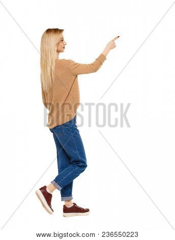 Side view of a girl walking with a pointing hand. going girl showing.  backside view of person.  Rear view people collection. The blonde in the sneakers demonstrates something