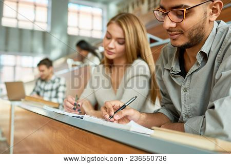 Multi-ethnic Group Of Students Sitting At Desk In Lecture Hall Of Modern College And Writing, Focus