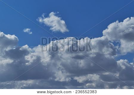Cumulus Clouds In The Clear Blue Sky. Rainy Dark Clouds In The Background. From Above White Clouds,