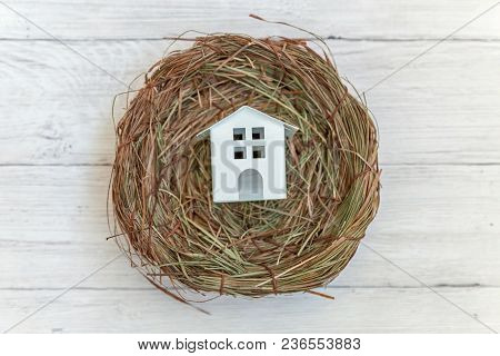Miniature White Toy Model House Rests In Nest On Rustic Old Vintage White Wooden Background. Eco Vil