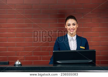 Young Beautiful Hotel Receptionist At Workplace Looking At Camera
