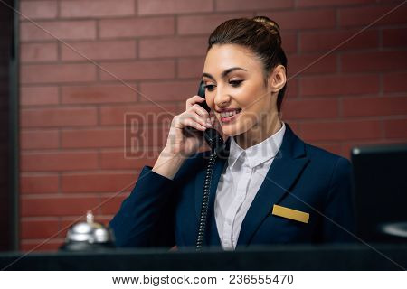 Young Beautiful Hotel Receptionist Receiving Call At Workplace