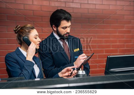Concentrated Hotel Receptionists Receiving Call From Customer At Workplace