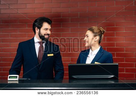 Hotel Receptionists Looking At Each Other By Counter