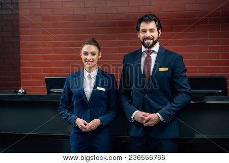Hotel Receptionists Standing Together In Front Of Counter And Looking At Camera