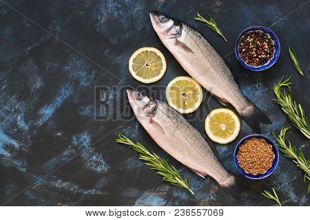 Raw Fish With Spices And Lime On A Blue Background. Sea Bass On A Blue Abstract Background, Top View