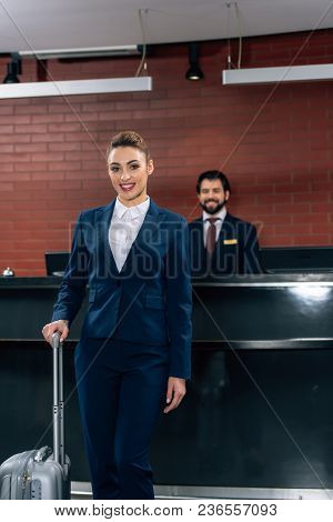 Happy Businesswoman With Luggage Standing In Front Of Hotel Reception Counter With Administrator