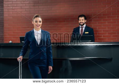 Smiling Businesswoman With Luggage Standing In Front Of Hotel Reception Counter With Administrator