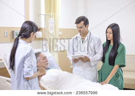 Doctor And Team Visit To Elderly Patient At Hospital Room. Healthcare And Medical Concept.