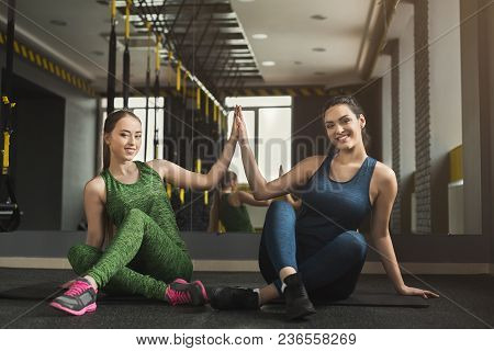 Two Happy Women Exercising At Fitness Club. Sporty Female Friends Giving High-five, Smiling At Camer