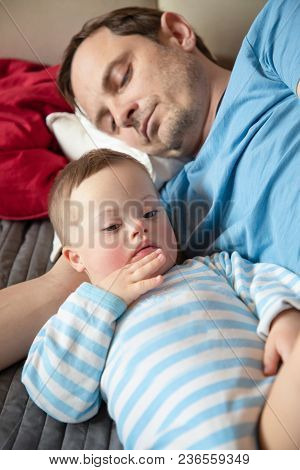 Cute Baby Boy With Down Syndrome Playing With Dad On In Home Living Room