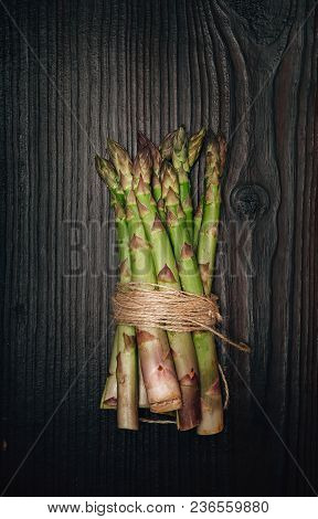 Green Asparagus Bundle On Dark Wooden Background