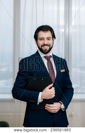 Handsome Hotel Administrator With Clipboard Looking At Camera