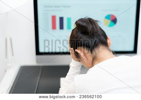 Feeling Tired And Stressed. Young Woman Suffer From Working While Sitting At Her Working Place In Of