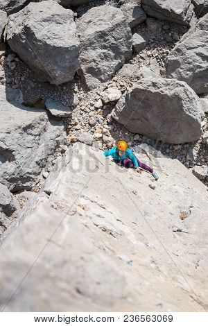 Mountaineer In Helmet. A Woman Climbs The Rock. The Girl Is Engaged In Extreme Sports In Nature. Ins