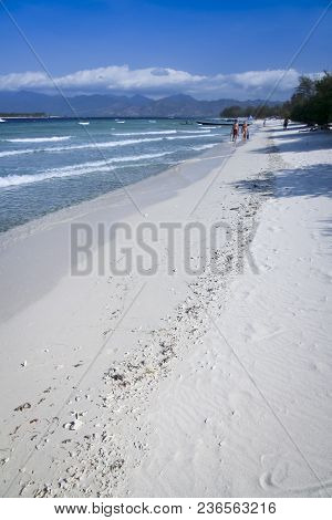 Tourist Couple Walking With Snorkels On The White Sand Beach Of Gili Trawangan Island In Indonesia
