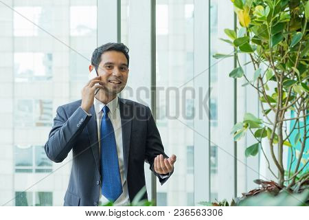 Businessman Using Mobile Phone Near Office Window At Receptions Area,negotiation Concept.
