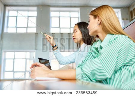 Side View Portrait Of Two Pretty Girls In College, One Of Them Asian, Sitting At Desk In Auditorium