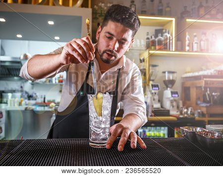 Bartender In A White Shirt And Black Apron, Adding A Slice Of Ginger Into A Glass