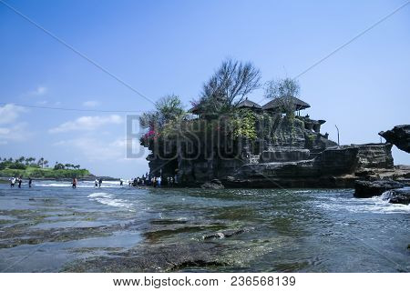Tourists Crossing To The Landmark Sea Temple Of Tanah Lot On The Coast Of Bali Indonesia