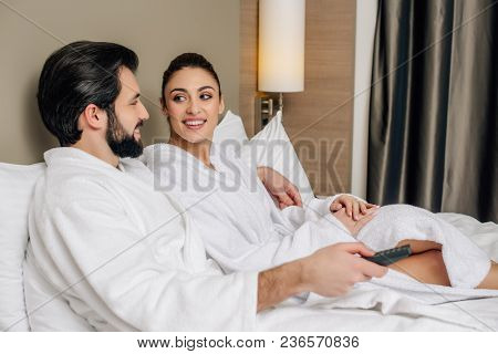 Happy Couple In Bathrobes With Tv Remote Control Relaxing In Bed At Hotel Suite